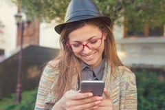 Donna abbastanza alla moda che per mezzo dello smartphone all'aperto fotografia stock