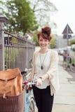 Donna abbastanza alla moda con la sua bicicletta Fotografie Stock