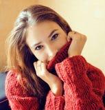 Donna abbastanza alla moda dei giovani in maglione rosso di inverno allo strato nel hom Fotografia Stock