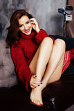 Donna abbastanza alla moda dei giovani in maglione rosso di inverno allo strato nel sorridere felice interno domestico, concetto  Fotografia Stock