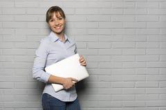Donna abbastanza allegra che tiene un computer portatile, isolato sopra un Br grigio Fotografia Stock Libera da Diritti