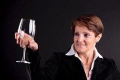 Donna abbastanza anziana che aumenta su un bicchiere di vino (fronte del fuoco) Immagine Stock