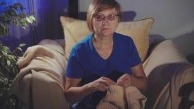 Donna abbastanza anziana che tricotta seduta sulla sedia stock footage