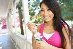 Donna abbastanza asiatica che mangia yogurt Fotografia Stock