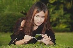 Donna abbastanza asiatica con la lente d'ingrandimento. Immagini Stock Libere da Diritti