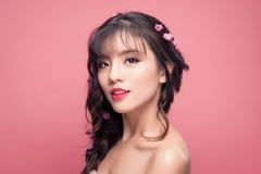 Donna abbastanza asiatica dei giovani con i fiori sulla fine dei capelli su sulla b rosa fotografie stock