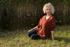 Donna abbastanza bionda che si siede sull'erba vicino al lago nel parco di autunno immagini stock