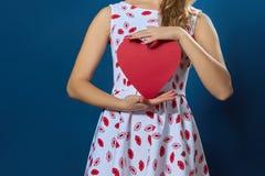 Donna abbastanza bionda che tiene cuore di carta rosso Fotografie Stock