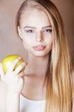 Donna abbastanza bionda dei giovani con la fine sorridente allegra felice della mela verde su su fondo marrone caldo, la gente di Immagine Stock Libera da Diritti