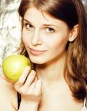 Donna abbastanza bionda dei giovani con la fine sorridente allegra felice della mela verde su su fondo marrone caldo, la gente di Fotografia Stock Libera da Diritti