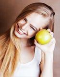 Donna abbastanza bionda dei giovani con la fine sorridente allegra felice della mela verde su su fondo marrone caldo, la gente di Fotografia Stock
