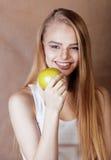 Donna abbastanza bionda dei giovani con la fine sorridente allegra felice della mela verde su su fondo marrone caldo, la gente di Immagini Stock Libere da Diritti
