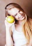 Donna abbastanza bionda dei giovani con sorridere allegro felice della mela verde Fotografia Stock