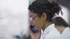 Donna abbastanza biraziale che parla sul cellulare, persuadente cliente a fare un acquisto video d archivio