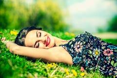 Donna abbastanza castana che si rilassa sull'erba del te nel parco fotografia stock