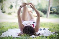 Donna abbastanza castana che utilizza smartphone nel parco Fotografia Stock Libera da Diritti