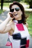 Donna abbastanza castana che utilizza smartphone nel parco Fotografie Stock