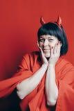 Donna abbastanza castana con i corni del diavolo rosso Fotografie Stock