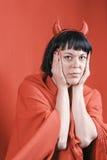 Donna abbastanza castana con i corni del diavolo rosso Fotografie Stock Libere da Diritti