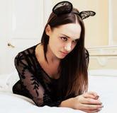 Donna abbastanza castana dei giovani che indossa le orecchie di topo sexy del pizzo, situantesi immagini stock