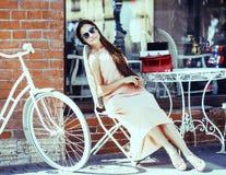 Donna abbastanza castana dei giovani dopo la seduta di compera al caffè fuori sul sorridere della via immagini stock