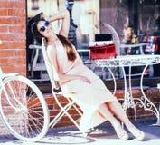 Donna abbastanza castana dei giovani dopo la seduta di compera al caffè fuori sul sorridere della via fotografia stock libera da diritti