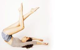 Donna abbastanza castana dei giovani gambe all'aria su bianco isolato Immagini Stock Libere da Diritti