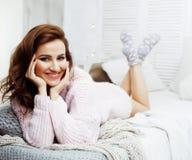 Donna abbastanza castana dei giovani nella sua camera da letto che si siede alla finestra, concetto sorridente felice della gente Immagini Stock