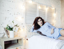Donna abbastanza castana dei giovani nella sua camera da letto che si siede alla finestra, concetto sorridente felice della gente Fotografia Stock