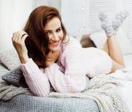 Donna abbastanza castana dei giovani nella sua camera da letto che si siede alla finestra, concetto sorridente felice della gente Immagine Stock Libera da Diritti