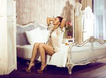 Donna abbastanza castana dei giovani nella sua camera da letto che si siede alla finestra, ha Fotografia Stock