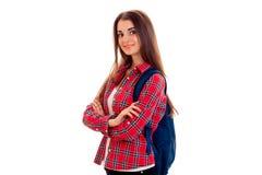 Donna abbastanza castana dello studente dei giovani con lo zaino blu sulla sua spalla che esamina la macchina fotografica e sorri Immagini Stock Libere da Diritti