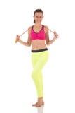 Donna abbastanza castana nelle ghette gialle al neon di sport ed in reggiseno rosa che posano con il salto della corda lungo Fotografie Stock