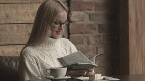 Donna abbastanza caucasica che legge una rivista ad un caffè video d archivio