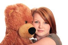 Donna abbastanza giovane che abbraccia un orso dell'orsacchiotto Fotografie Stock