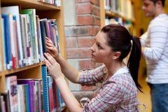 Donna abbastanza giovane che cerca un libro Immagini Stock
