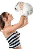 Donna abbastanza giovane che gioca con il coniglio Fotografia Stock