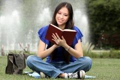 Donna abbastanza giovane che legge un libro alla sosta Immagine Stock Libera da Diritti