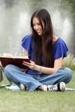 Donna abbastanza giovane che legge un libro alla sosta Fotografia Stock