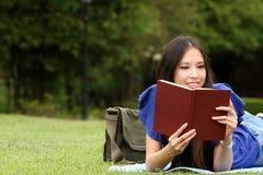 Donna abbastanza giovane che legge un libro alla sosta Fotografia Stock Libera da Diritti