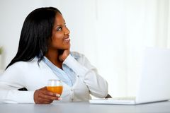 Donna abbastanza giovane che osserva in su con un succo di arancia Immagine Stock Libera da Diritti