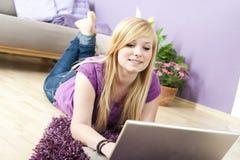 Donna abbastanza giovane che per mezzo del computer portatile Fotografia Stock