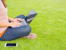 Donna abbastanza giovane che per mezzo del computer portatile Immagini Stock