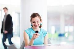 Donna abbastanza giovane che per mezzo del suo telefono mobile Immagine Stock