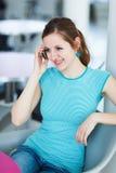 Donna abbastanza giovane che per mezzo del suo telefono mobile Fotografia Stock