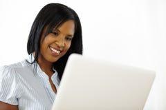 Donna abbastanza giovane che per mezzo di un computer portatile Fotografia Stock Libera da Diritti