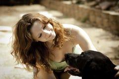 Donna abbastanza giovane che petting il suo cane Immagine Stock