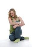 Donna abbastanza giovane che si siede con le braccia attraversate Fotografia Stock