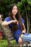 Donna abbastanza giovane che si siede sul banco Immagine Stock