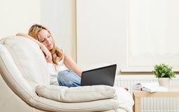 Donna abbastanza giovane che si siede sul sifa con il computer portatile Fotografie Stock Libere da Diritti